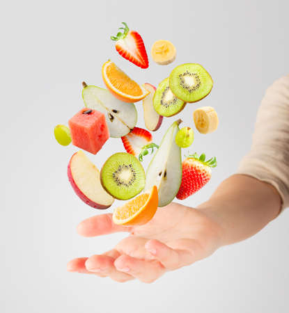 Assorted fresh fruits flying in a hand