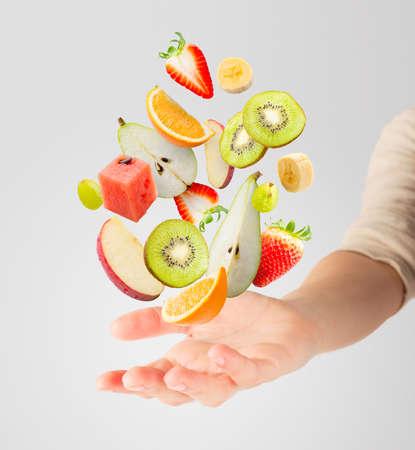 Verschiedene frische Früchte fliegen in einer Hand Standard-Bild