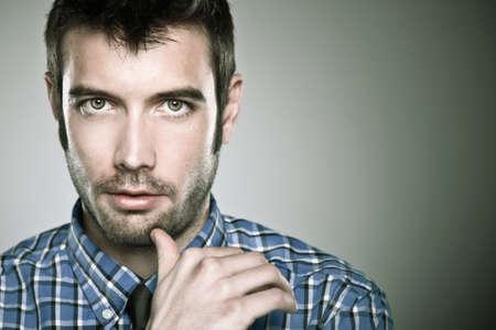 při pohledu na fotoaparát: Mladý muž tvář, vysoce detailní portrét. Reklamní fotografie