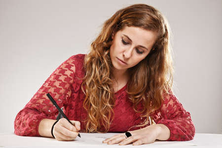 writing book: Portrait of a young woman over grey background Stock Photo
