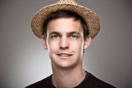 straw hat: Portrait of a normal young man with straw hat on a grey background