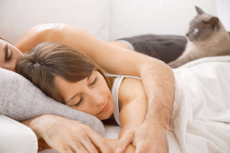 cat sleeping: Lovely couple resting in bedroom Stock Photo
