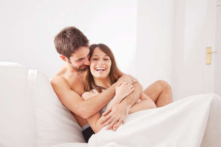 Young happy couple in bedroom photo