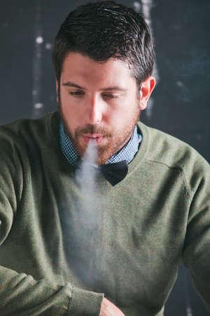 man smoking: Caucasian man sitting and smoking  Stock Photo