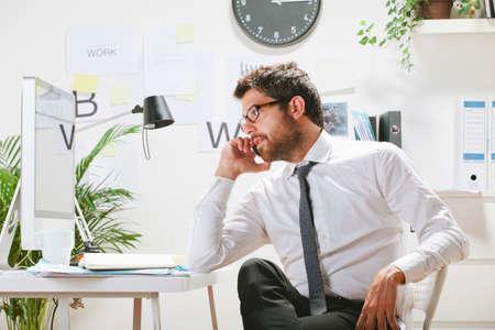 コンピューターを見て縁のメガネを持ったビジネスマン