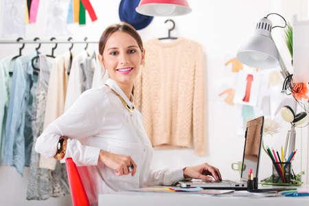 Jonge creatieve vrouw in haar kantoor kijken naar de camera Stockfoto