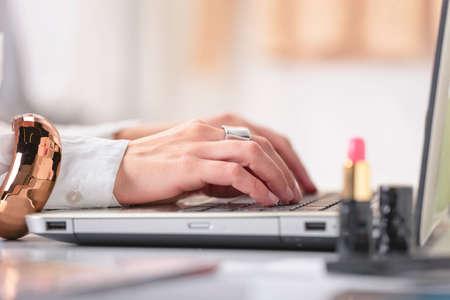 Jonge creatieve vrouw te typen op een laptop in haar kantoor