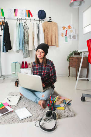 Young creative woman sitting in the floor with laptop  photo