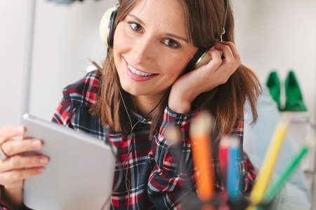 Young creative woman listening music with headphones, photo