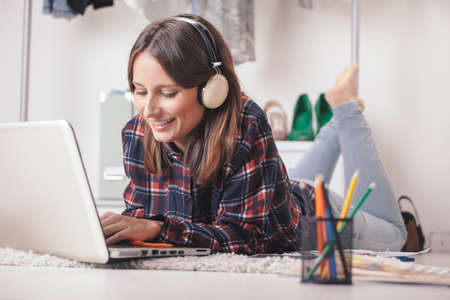 blogger: Young creative woman stretched in the floor and listening music  Stock Photo