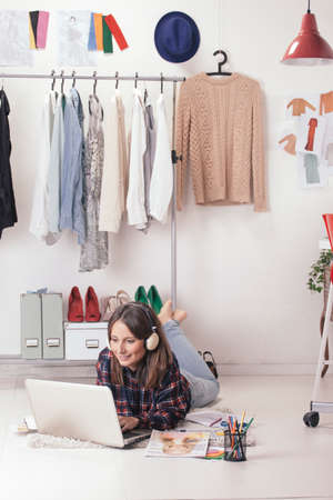 personal shopper: Young creative woman stretched in the floor and listening music  Stock Photo