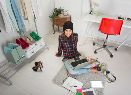 blogger: Young creative woman sitting in the floor with laptop  Stock Photo
