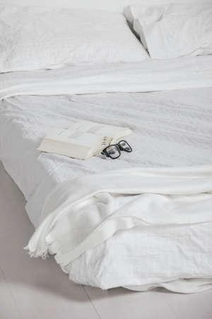 rimmed: El Primer dormitorio blanco del libro viejo y gafas de montura en la cama Foto de archivo