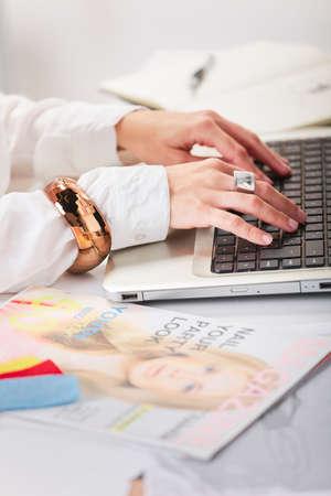 若い創造的な女性彼女のオフィスでラップトップ上で入力