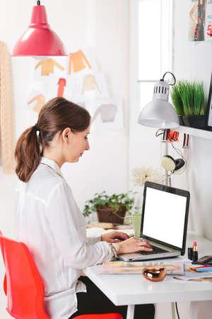 Mujer joven escribiendo creativa en un ordenador portátil en su oficina Foto de archivo - 24404551
