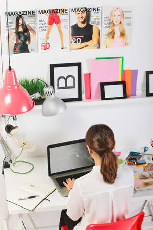 Young creative woman typing on a laptop in her office