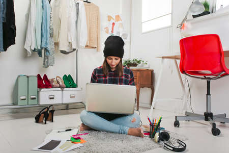 Young creative woman sitting in the floor with laptop  Stock Photo