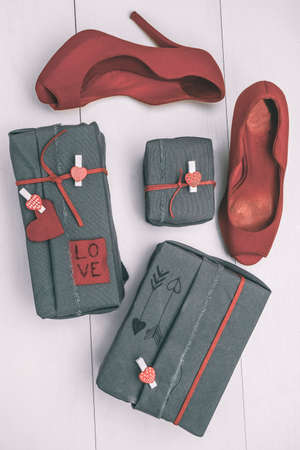 heeled: Valentines gifts box with hipster ornaments and red heeled shoes