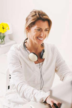 Smiling mature woman sitting on desk  photo