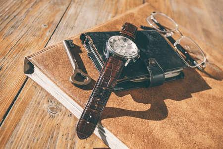 Man horloge, kalender, sleutel en glazen op een oude tafel Stockfoto