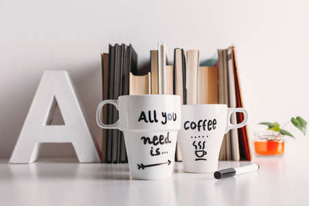 Hipster cup of coffee on a books library