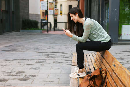bench alone: Young woman sitting on a bench in the city.