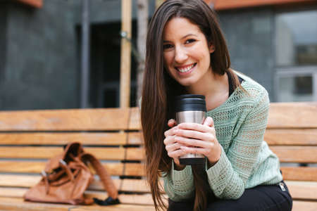 thermos: Smiling woman sitting on a bench in the city. Stock Photo