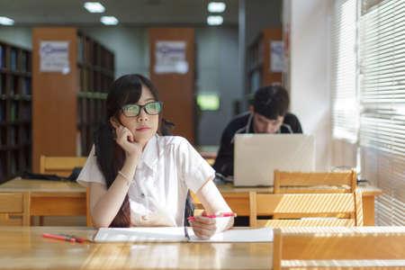 estudiando: Chica asi�tica en uniforme que estudia en biblioteca Foto de archivo