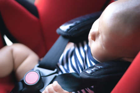 Asian baby sleeping in carseat