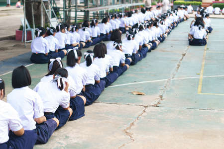 Thai students sit on the floor for school morning announce