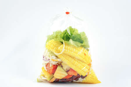 plastic bag: Salad packed in plastic bag on white background