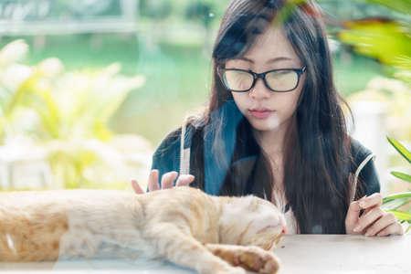 amigos abrazandose: Asia chica con gafas jugando con el gato
