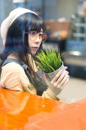 Charming Asian girl holding pot with a plant . Stock Photo