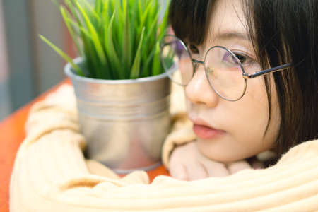 bib overall: Charming Asian girl holding pot with a plant . Stock Photo
