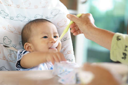 6 years old Asian baby eating food for the first time Stock Photo