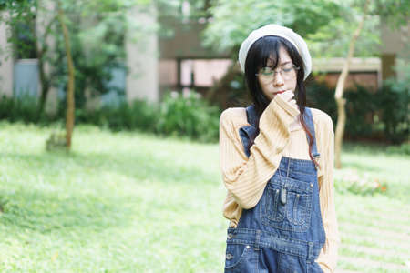 Charming Asian girl wearing jean overalls in the park Stock Photo