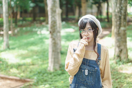 bib overall: Charming Asian girl wearing jean overalls in the park Stock Photo