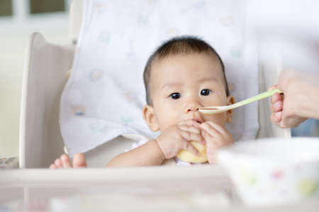 7 months old Asian baby eating fruit for the first time Stock Photo