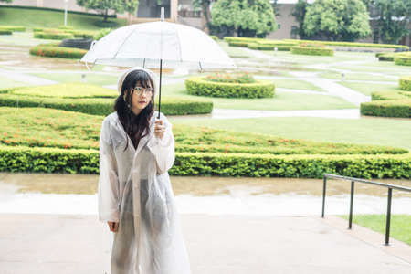 rain wet: Charming Asian girl  with umbrella and raincoat on raining day