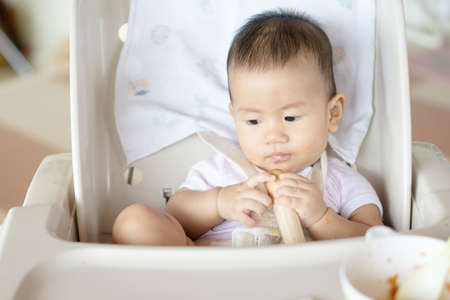7 months: 7 months old Asian baby eating fruit for the first time Stock Photo