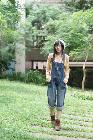 overalls: Charming Asian girl wearing jean overalls in the park Stock Photo