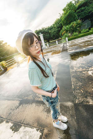 Charming Asian girl wearing jean overalls with sunset as background