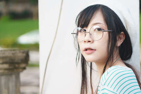 Portrait of charming Asian girl wearing jean overalls in the park