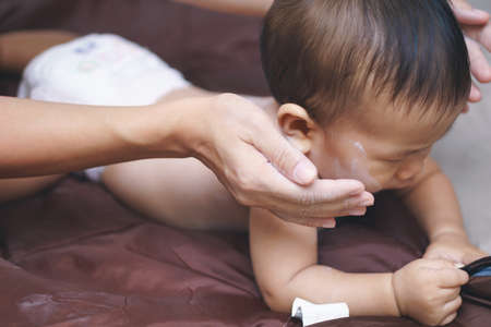 Mother applying baby powder to her son Stock Photo