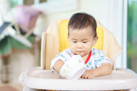 baby rice: 8 months old Asian baby eating food by himself Stock Photo