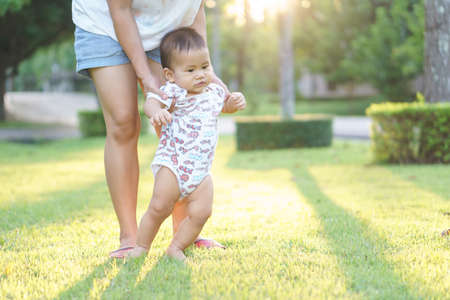 Mother helping Asian baby to learn first step on a lawn in summer day