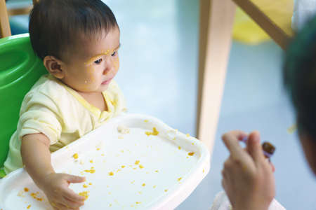 9 months old Asian baby refuses eating medicine after meal Stock Photo