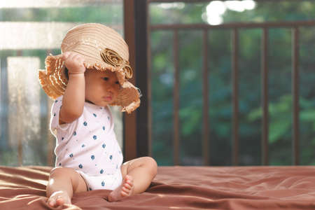 9 months Asian baby playing with hat on the bed