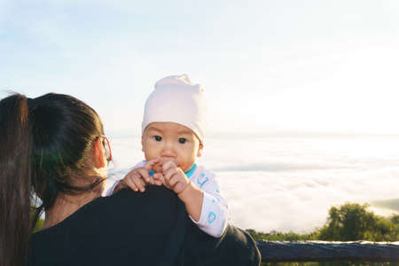 Asian Mother holding her baby to see the fog over mountain