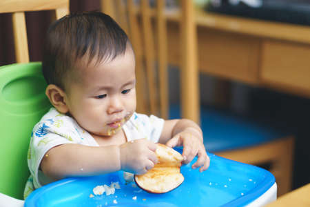 baby rice: 9 months old Asian baby eating food by himself Stock Photo
